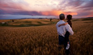 Grandfather and grandson (4-5) in wheat field at sunset